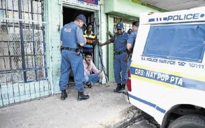 Nazil Munssi, surrounded by police, in front of his looted shop on Friday. Townships including Soweto have been hit by looters targeting foreign-owned stores. Picture: AFP/STEFAN HEUNIS